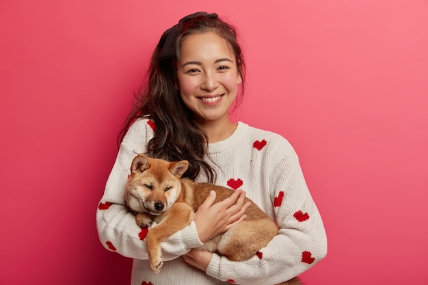 Positive asian girl gets cute shiba inu puppy as present, ready to care about domestic pet, likes playing with animals, spend day together.