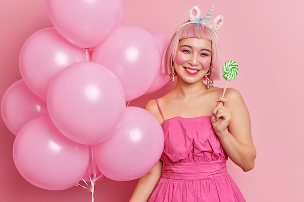 Positive asian girl smiles gently has bright makeup wears dress holds delicious sweet candy bunch of inflated balloons enjoys holiday celebrates birthday being on party