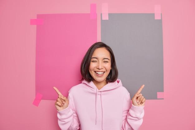La ragazza hipster asiatica positiva indossa una felpa con cappuccio casual suggerisce di controllare il collegamento o il banner indica il dito indice nello spazio vuoto della copia