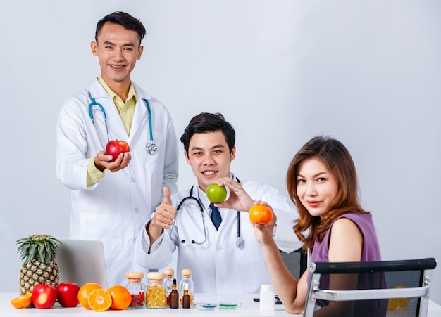 Positive asian male nutritionists with fruits and healthy food gathering at table with female patient while looking at camera on white background