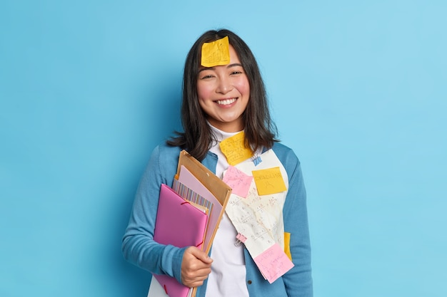 Positive asian student holds folders stands glad with stickers on clothes and forehead prepares project work in economics happy to finish doing important task wears jumper.