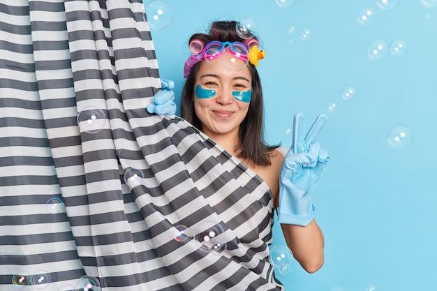 Positive asian woman enjoys showering applies hair curlers