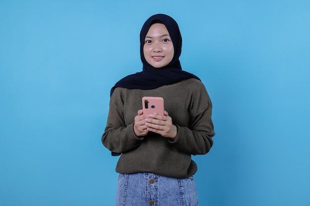 긍정적인 아시아 여성 소녀는 엄지손가락을 가리키고 스마트폰을 가져와 빈 파란색 벽에 복사 공간을 보여줍니다