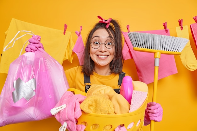 Positive asian woman holds broom for sweeping floor poses with cleaning supplies polythene bag full of detergents does laundry at home busy doing housework and domestic duties. housecleaning
