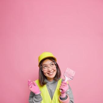 쾌활한 표정으로 긍정적 인 아시아 여성이 페인트 브러시를 보유하고 아파트를 개선하는 방법을 생각하고 유니폼을 입고 건설 계획을 이행하려고합니다.