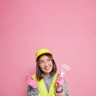 Positive asian woman looks above with cheerful expression holds paint brush thinks how to improve apartment tries to fulfill construction plan dressed in uniform