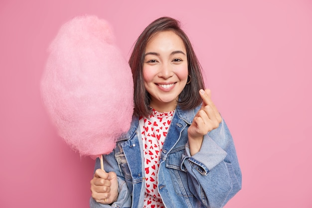 La donna asiatica positiva rende il segno coreano come esprime i sorrisi d'amore esprime piacevolmente l'amore vestito con una giacca di jeans tiene zucchero filato su forme di bastone mini cuore isolato sul muro rosa