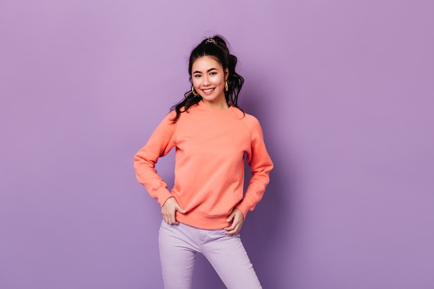 엉덩이에 손으로 서 긍정적 인 아시아 여자. 카메라에 미소 자신감 일본 젊은 여자.