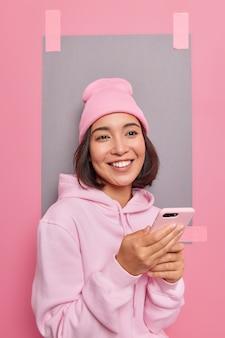 夢のような表情でポジティブなアジアの女性がアプリの巻物でスマートフォンのチャットを保持しますソーシャルネットワークは快適な服を着てインターネットで何かを注文します屋内の本のタクシー