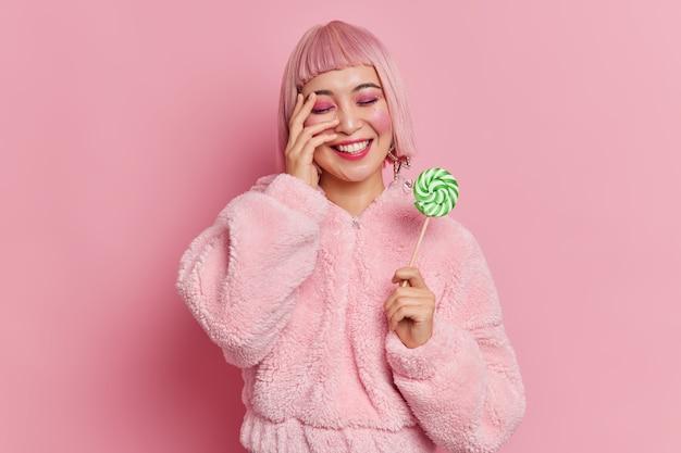 ピンクの髪のポジティブなアジアの女性は明るい化粧をしていて、スティックにおいしいお菓子を持っています
