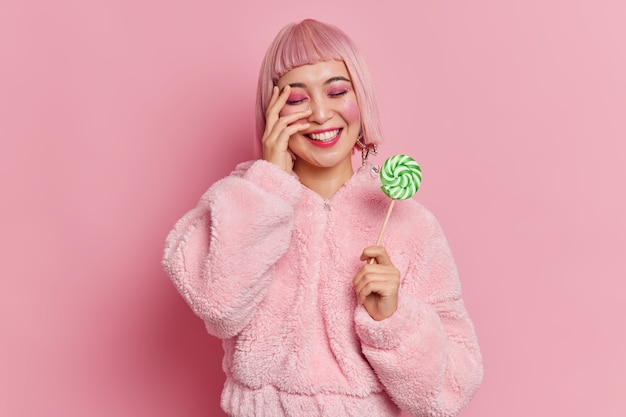 La donna asiatica positiva con i capelli rosa ha un trucco luminoso che tiene deliziose caramelle sul bastone