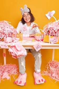 Positive asian woman works from home during quarantine or lockdown dressed in nightwear prepares course work surrounded by cut paper poses at messy room against yellow wall
