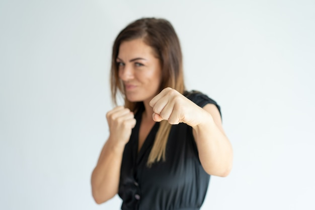 Positive athletic businesswoman punching at camera.
