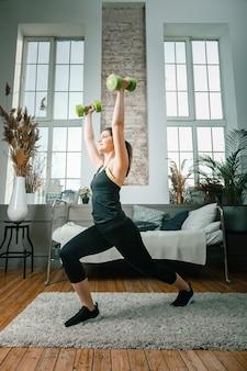 Позитивная спортивная женщина с аккуратно завязанными волосами и в обтягивающей спортивной одежде делает выпады с гантелями дома
