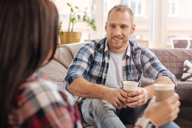 ポジティブな雰囲気。一杯のコーヒーを持って、彼の同僚と楽しい時間を過ごしながら笑顔で陽気なハンサムな魅力的な男