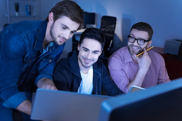 Positive atmosphere. delighted handsome good looking programmers looking at the laptop screen and smiling while being amused by something