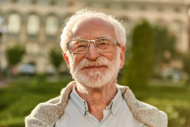 Positive attitude portrait of handsome bearded senior man in glasses looking at camera and smiling