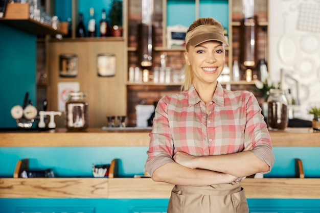 Positive attitude of the waitress. blonde is standing in a cafe and wearing a plaid shirt and apron. she has her arms crossed and looking straight at the camera with a smile. morning coffee and brunch