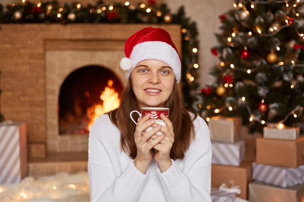 Positive attractive dark haired woman wearing white sweater and santa claus hat sitting in cozy decorated living room near xmas tree and fireplace, holding cup of hot coffee or tea.