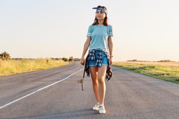 Donna attraente positiva che indossa pantaloncini, maglietta e fascia per capelli che tiene lo skateboard in mano e distoglie lo sguardo, camminando su strada asfaltata al tramonto in estate.