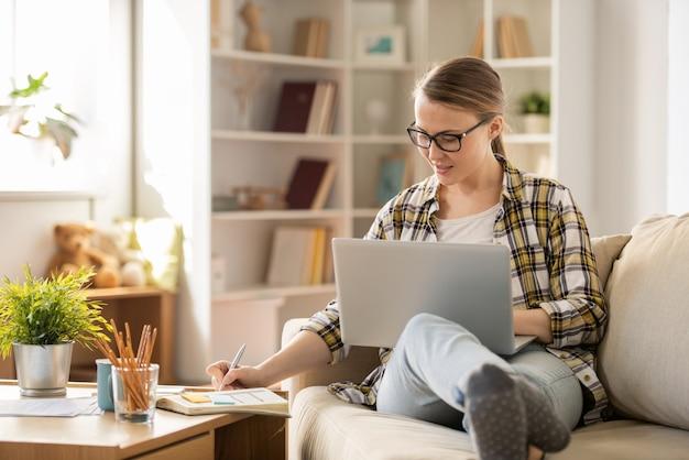 ソファーに座って、自宅で仕事をしながら日記にメモをとるメガネの肯定的な魅力的な女の子