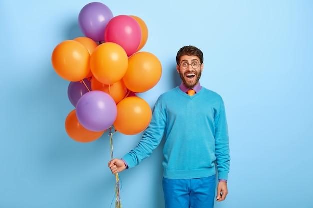 Uomo attraente positivo con sguardo felice, indossa occhiali rotondi, vestito blu