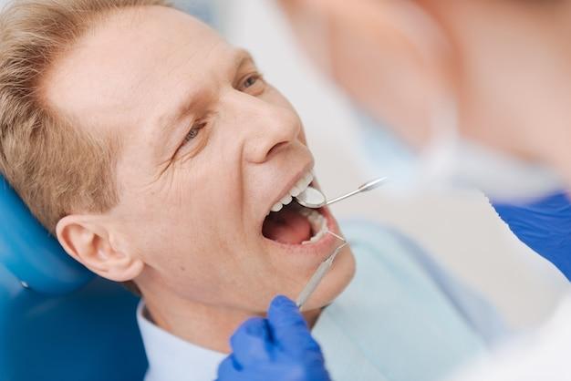그의 구멍을 건강하게 유지하고 치료하지 않기 위해 치과 의사에게 방문을 지불하는 긍정적 인 매력적인 성숙한 남자