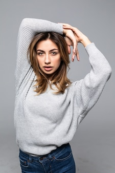 Positive attractive woman wears casual sweater isolated against gray wall