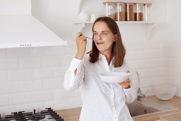 白いカジュアルなシャツを着て黒髪のポジティブな魅力的な若い大人の女性。朝食をとり、皿を手に持ち、目をそらし、スプーンで食べる。