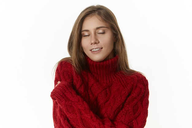 Positive attractive young caucasian woman with long loose hair closing eyes with pleasure, keeping arms around shoulders, enjoying warm cozy knitted sweater, smiling joyfully