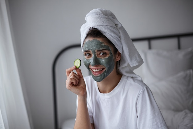 Positive attractive young dark haired woman with cosmetic mask of blue clay on her face applying fresh cucumber on her eye and smiling cheerfully, isolated over home interior
