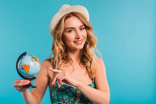 Positive attractive young woman in hat and dress showing globe
