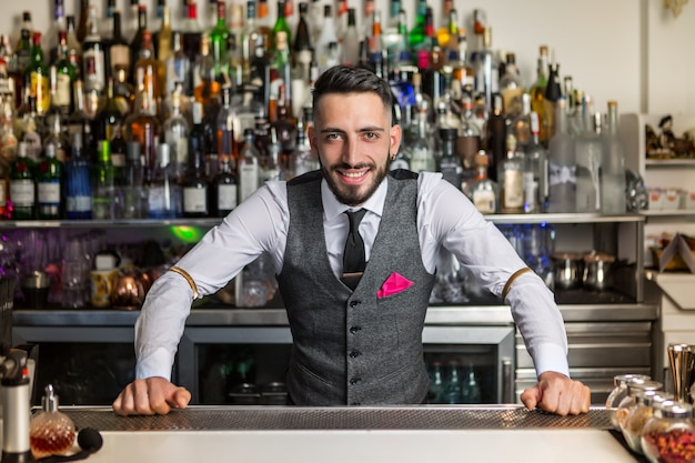 Positive barkeeper standing at counter