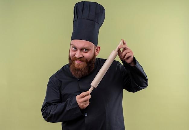 Un uomo di chef barbuto positivo in uniforme nera che mostra il suo mattarello mentre guarda su una parete verde