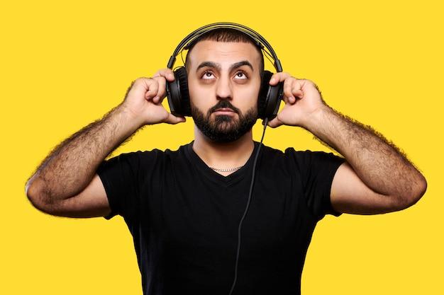 노란색 웃음 헤드폰 긍정적 인 수염 된 dj. 음악을 즐기십시오. 국제 dj의 날.