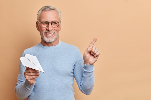 Positive bearded grey haired senior man thinks about traveling abroad holds handmade paper plane indicates at upper right corner wears casual jumper isolated over brown wall shows copy space