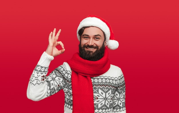 Positive bearded guy in stylish sweater and santa hat