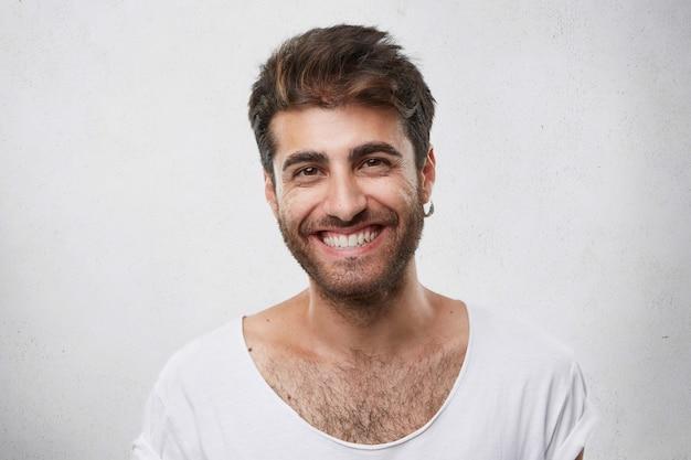 Позитивный бородатый парень с темными теплыми глазами с серьгой в ухе, одетый небрежно, с приятной улыбкой, демонстрирует свои идеальные белые зубы с хорошим настроением