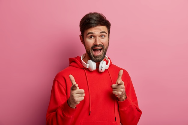 Positive bearded hipster guy points directly at you, makes good choice, says excellent, makes its up to you gesture, wears red hoodie and modern headphones, poses against pink pastel wall