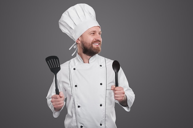 Positive bearded male cook in white chef uniform holding spatula and spoon and looking away while standing against gray background