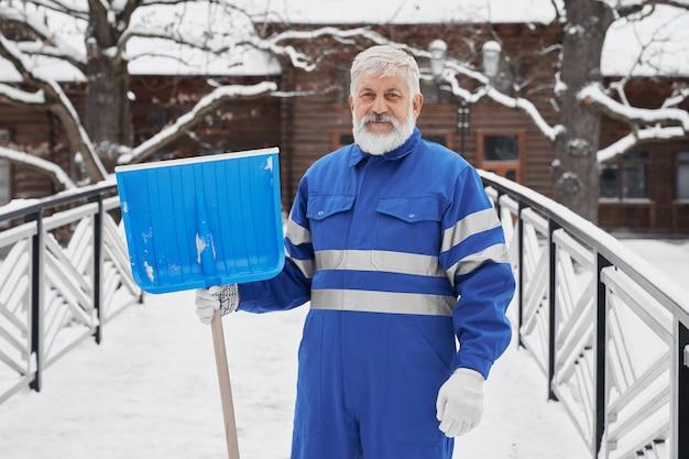 Позитивный бородатый мужчина держит лопату в руке зимой