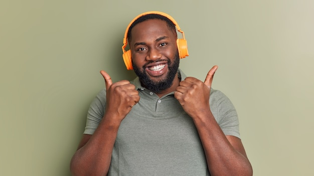 Positive bearded man likes playlist keeps thumbs up makes approval gesture listens music via headphones smiles toothily dressed in casual t shirt isolated over dark green wall