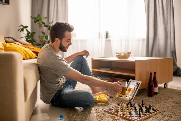 Позитивный бородатый мужчина сидит на полу и пьет пиво с другом, общаясь онлайн в домашней изоляции