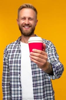 Позитивный бородатый мужчина с кофе на вынос