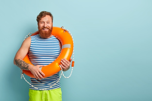 Positive bearded red haired guy wears striped sailor vest, carries orange lifebuoy