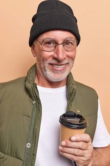 세련된 옷을 입은 긍정적인 수염 난 노인은 테이크아웃 커피를 마신다 상쾌한 향기로운 음료를 마시는 것을 즐긴다