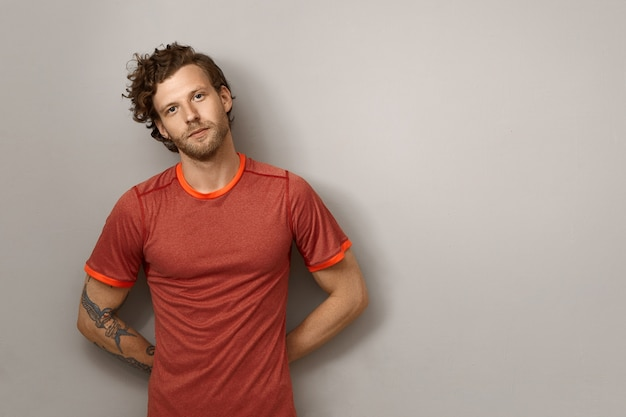 Positive bearded young male runner with curly hairdo and tattoo on muscular arm leaning on blank copyspace wall, keeping hands behind his back. fit athletic macho man posing isolated