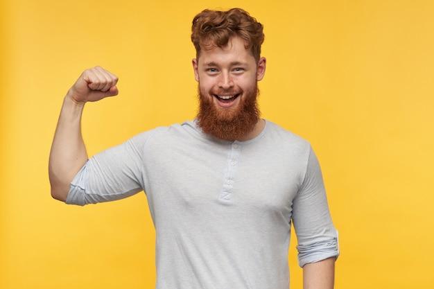ポジティブなあごひげを生やした若い男性は広く笑顔で、彼の上腕二頭筋を世界に示しています。ポジティブな男は黄色で隔離された彼の筋肉を示しています