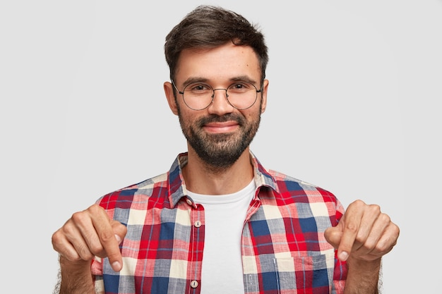 Positive bearded young man points down with glad satisfied expression, demonstrates something on floor