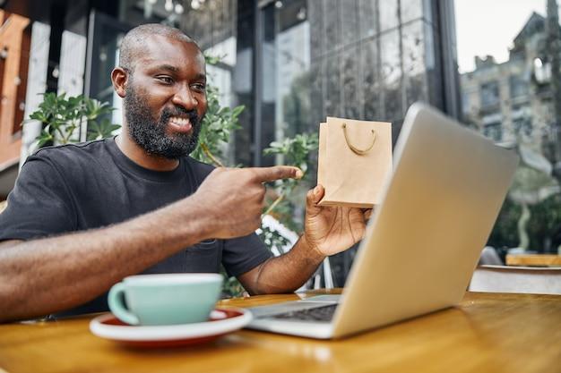 긍정적 인 수염 난 젊은이 커피 한잔과 함께 테이블에 앉아 웹 카메라를 보면서 종이 봉지를 가리키는